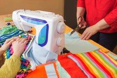 Mains d'ouvrière couturière sur la table de travail avec le modèle et la bande de mesure Un tailleur présente une robe Photographie stock libre de droits