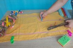 Mains d'ouvrière couturière sur la table de travail avec le modèle et la bande de mesure Photo stock