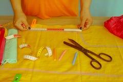 Mains d'ouvrière couturière sur la table de travail avec le modèle et mesurer merci Images libres de droits