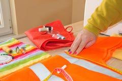 Mains d'ouvrière couturière sur la table de travail avec le modèle et mesurer merci Photo stock