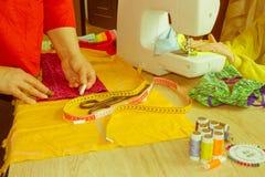 Mains d'ouvrière couturière sur la table de travail avec le modèle et mesurer merci Photographie stock libre de droits