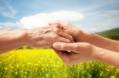 Mains d'un aîné plus âgé tenant la main d'une femme Photographie stock