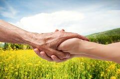 Mains d'un aîné plus âgé tenant la main d'une femme Images libres de droits