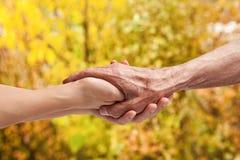 Mains d'un aîné plus âgé tenant la main d'une femme Photos stock