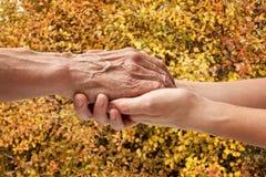 Mains d'un aîné plus âgé tenant la main d'une femme Image libre de droits