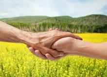 Mains d'un aîné plus âgé tenant la main d'une femme Image stock