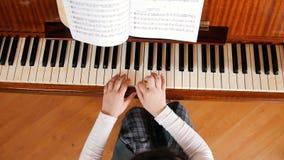 Mains d'un bébé jouant le piano sur la leçon de musique à l'école Angle supérieur images stock