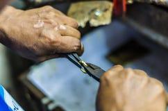 Mains d'un bijoutier travaillant à un anneau avec des pinces photos libres de droits