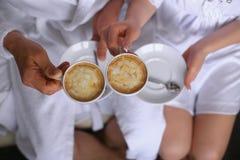Mains d'un couple affectueux tenant des tasses de café au-dessus d'une table dans la chambre d'hôtel Photographie stock libre de droits