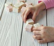 Mains d'un enfant faisant des constructions des blocs photos stock