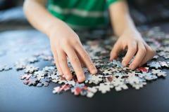 Mains d'un enfant faisant un puzzle Photos libres de droits