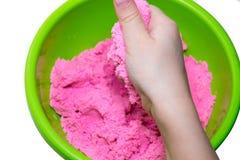 Mains d'un enfant jouant avec le sable magique rose images stock