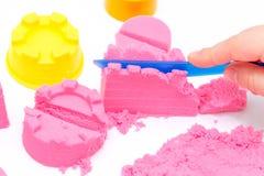 Mains d'un enfant jouant avec le sable magique rose photos libres de droits