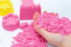 Mains d'un enfant jouant avec le sable magique rose images libres de droits