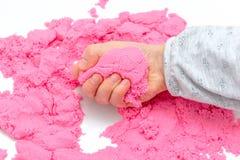 Mains d'un enfant jouant avec le sable magique rose image stock