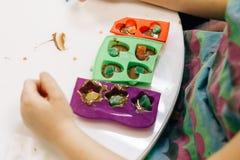 Mains d'un enfant, d'une classe principale en faisant cuire le chocolat, de fruit se pliant et de chocolat dans des moules images stock