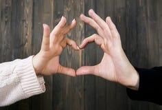 Mains d'un homme et d'une fille empilés ensemble dans une forme de coeur Photos stock