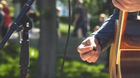 Mains d'un homme jouant une guitare acoustique banque de vidéos