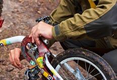 Mains d'un homme réparant une bicyclette Image stock
