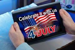 Mains d'un homme regardant en Web un site avec l'information du 4 juillet Image stock