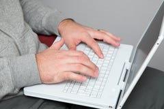 Mains d'un homme sur le clavier d'ordinateur portatif Photographie stock libre de droits