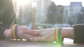 Mains d'un jeune ajouter aux bracelets de LGBT sur le fond de la rue, derrière une table banque de vidéos