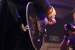 Mains d'un musicien de roche avec la guitare électrique acoustique Photographie stock