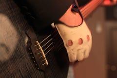 Mains d'un musicien de roche avec la guitare électrique acoustique Photo libre de droits