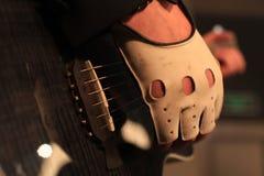 Mains d'un musicien de roche avec la guitare électrique acoustique Image stock