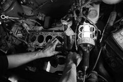 Mains d'un ouvrier réparant le véhicule Photographie stock libre de droits