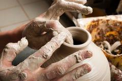 Mains d'un potier, produisant un choc de terre Photos stock