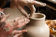 Mains d'un potier, produisant un choc de terre Photo stock