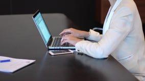 Mains d'une femme d'affaires utilisant un ordinateur portable avec la stat banque de vidéos