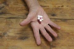 Mains d'une femme agée avec des pilules Photographie stock