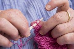 Mains d'une femme faisant du crochet avec le crochet en ivoire images stock