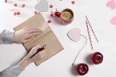 Mains d'une femme qui va dessiner par un crayon dans un carnet Sur la table il y a une tasse de thé avec le citron, les pommes et Photographie stock