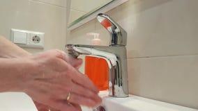 Mains d'une femme se lavant les mains avec du savon sous le robinet banque de vidéos