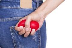 Mains d'une femme serrant une boule d'effort Photographie stock libre de droits