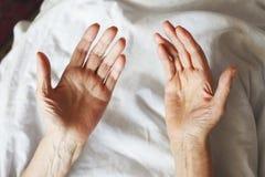 Mains d'une femme supérieure sur la canne Se situer supérieur dans un lit Photo libre de droits