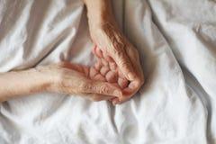 Mains d'une femme supérieure sur la canne Se situer supérieur dans un lit Images stock