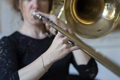 Mains d'une fille jouant le trombone image stock