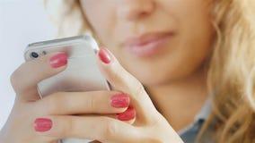 Mains d'une jeune femme avec un téléphone portable, lèvres de sourire légèrement brouillées clips vidéos