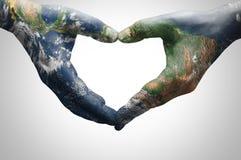 Mains d'une jeune femme formant un coeur modelé avec une carte du monde meublée par la NASA photos libres de droits