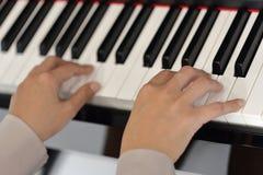 Mains d'une jeune femme jouant le piano Photos libres de droits