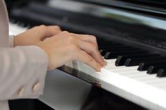 Mains d'une jeune femme jouant le piano Photographie stock