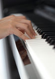 Mains d'une jeune femme jouant le piano Image stock