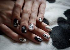 Mains d'une jeune fille avec la manucure noire et blanche sur un beau fond photo libre de droits
