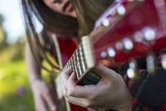 Mains d'une jeune fille sur les frettes de la guitare acoustique passe-temps images stock