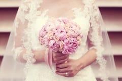 Mains d'une jeune mariée tenant le bouquet de pivoines Photographie stock libre de droits