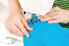 Mains d'une ouvrière couturière à la machine à coudre Image stock
